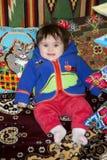 Bambina stupefacente che si siede a letto su un letto con i cuscini ricamati immagini stock libere da diritti