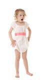Bambina stupita che si leva in piedi sulla priorità bassa bianca Fotografie Stock