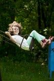 Bambina su un'oscillazione nel parco di estate Immagine Stock