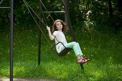 Bambina su un'oscillazione nel parco di estate Immagini Stock