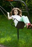 Bambina su un'oscillazione nel parco di estate Fotografie Stock Libere da Diritti