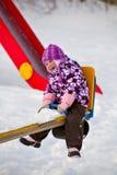 Bambina su un'oscillazione nell'inverno Fotografia Stock