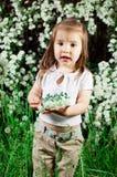 Bambina su una priorità bassa un cespuglio con i fiori Fotografie Stock Libere da Diritti
