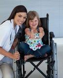 Bambina su una sedia a rotelle con il suo medico fotografie stock libere da diritti