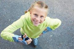 Bambina sui pattini di rullo in parco Ragazza felice Immagine Stock