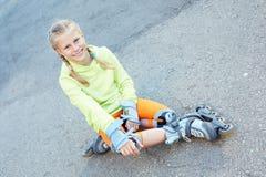 Bambina sui pattini di rullo in parco Ragazza felice Fotografia Stock