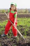 Bambina sul campo con lo strumento della zappa Immagini Stock