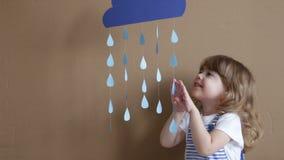 Bambina sul gioco grigio del fondo con le forme e la nuvola di goccia stock footage