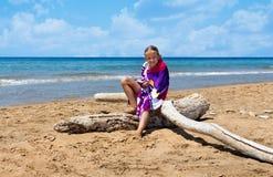 Bambina sulla spiaggia abbandonata soleggiata Fotografia Stock