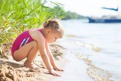 Bambina sulla sponda del fiume che tocca l'onda Immagini Stock Libere da Diritti