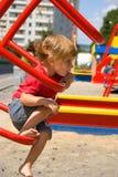 Bambina sulla strumentazione del campo da giuoco Immagine Stock