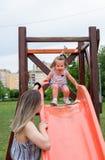 Bambina sullo scorrevole al campo da giuoco dei bambini Immagini Stock