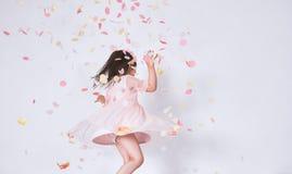 Bambina sveglia allegra che porta vestito rosa a Tulle con la corona di principessa che balla sulla sorpresa dei coriandoli sullo fotografie stock