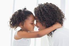 Bambina sveglia che abbraccia sua madre Immagini Stock Libere da Diritti