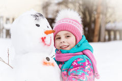 Bambina sveglia che abbraccia un pupazzo di neve Immagine Stock Libera da Diritti