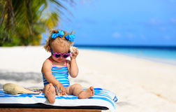 Bambina sveglia che ascolta le coperture sulla spiaggia Immagine Stock