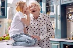 Bambina sveglia che bisbiglia in suo orecchio delle nonne Fotografie Stock