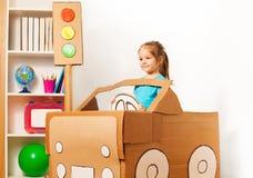 Bambina sveglia che conduce la sua automobile del cartone del giocattolo Immagini Stock