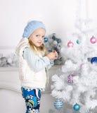 Bambina sveglia che decora l'albero di Natale Immagine Stock