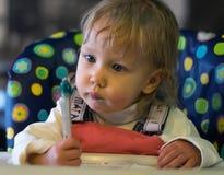 Bambina sveglia che esamina la penna nella sedia dei bambini Fotografie Stock Libere da Diritti