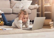 Bambina sveglia che fa compito sul computer portatile Fotografia Stock