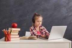 Bambina sveglia che fa compito sul computer portatile Immagini Stock