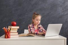 Bambina sveglia che fa compito sul computer portatile Fotografia Stock Libera da Diritti