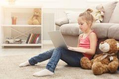 Bambina sveglia che fa compito sul computer portatile, sedentesi sul pavimento a casa Fotografia Stock