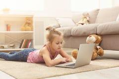 Bambina sveglia che fa compito sul computer portatile, sedentesi sul pavimento a casa Immagine Stock