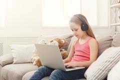 Bambina sveglia che fa compito sul computer portatile, sedentesi sullo strato in cuffie Fotografie Stock Libere da Diritti