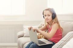 Bambina sveglia che fa compito sul computer portatile, sedentesi sullo strato in cuffie Fotografia Stock Libera da Diritti