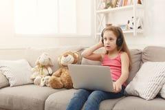 Bambina sveglia che fa compito sul computer portatile, sedentesi sullo strato in cuffie Fotografia Stock
