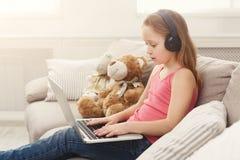 Bambina sveglia che fa compito sul computer portatile, sedentesi sullo strato in cuffie Fotografie Stock