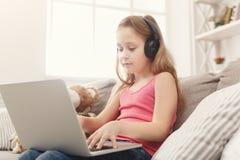 Bambina sveglia che fa compito sul computer portatile, sedentesi sullo strato in cuffie Immagine Stock Libera da Diritti