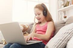 Bambina sveglia che fa compito sul computer portatile, sedentesi sullo strato in cuffie Immagine Stock