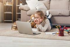 Bambina sveglia che fa compito sul computer portatile, trovantesi sul pavimento Fotografia Stock Libera da Diritti