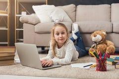 Bambina sveglia che fa compito sul computer portatile, trovantesi sul pavimento Immagini Stock