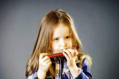 Bambina sveglia che gioca armonica Immagine Stock