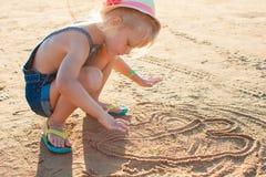 Bambina sveglia che gioca con la sabbia sulla spiaggia Immagini Stock