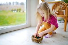 Bambina sveglia che gioca con le uova di Pasqua colorate a casa sul giorno di Pasqua Fotografia Stock Libera da Diritti