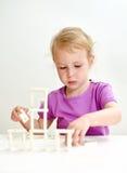 Bambina sveglia che gioca domino Immagini Stock Libere da Diritti