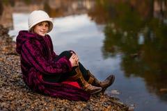 Bambina sveglia che gioca nel giorno di autunno vicino al lago Bambini felici divertendosi in autunno Ragazza vestita in cappotto immagine stock
