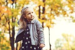 Bambina sveglia che gioca nel parco di autunno Bambino felice che gioca con le foglie cadute L'autunno scherza il modo Infanzia f fotografia stock