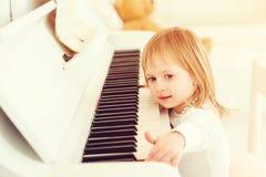 Bambina sveglia che gioca piano ad una scuola di musica Bambino prescolare che impara giocare lo strumento di musica Istruzione,  immagini stock