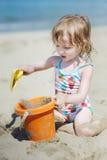 Bambina sveglia che gioca su una spiaggia fotografia stock libera da diritti
