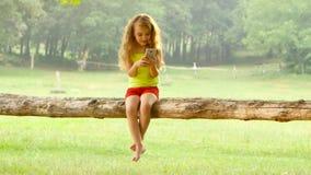 Bambina sveglia che gioca sullo smartphone che si siede su un albero stock footage