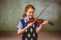 Bambina sveglia che gioca violino in aula Immagine Stock
