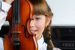 Bambina sveglia che giudica un violino dell'interno Fotografie Stock