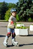 Bambina sveglia che impara pattinaggio a rotelle Fotografia Stock