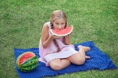 Bambina sveglia che mangia anguria sull'erba nell'ora legale con i capelli lunghi della coda di cavallo ed il sorriso a trentadue Immagini Stock